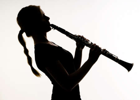 Female Musician Practices her Woodwind Technique on a Clarinet Photographed in silhouette Фото со стока