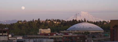 appears: A full moon appears on the horizon near Mt Rainier and the Tacoma Dome Stock Photo