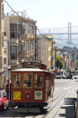 cable car: San Francisco, California, USA - August 8, 2012: A cable driven Market Street trolley car travels up the hill out of Chinatown with the Bay Bridge in the background.