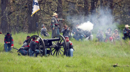 Steilacoom, Washington, USA - May 1, 2010: A group of confederate soldiers battle during a Civil War re-enactment in the Pacific Northwest Cannoneers in the foreground.