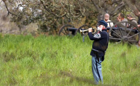 reenactment re enactment: Steilacoom, Washington, USA - May 1, 2010: A Union Army Bugler sounds a call during battle in a Civil War re-enactment in the Pacific Northwest Cannoneers in the background. Editorial