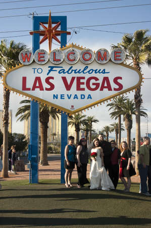 Las Vegas, Nevada, USA - April 1, 2010: People pose outside with bride and groom after a wedding under the welcome sign in Las Vegas. Редакционное