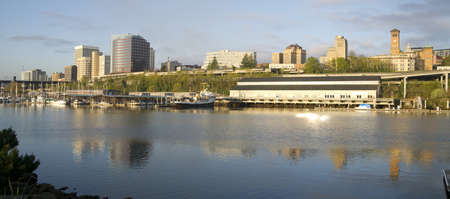 The sun rises hitting the waterfront and buildings of Downtown Tacoma Washington United States Stock Photo