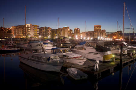 Night falls behind the Tacoma skyline and boats on Thea Foss Waterway