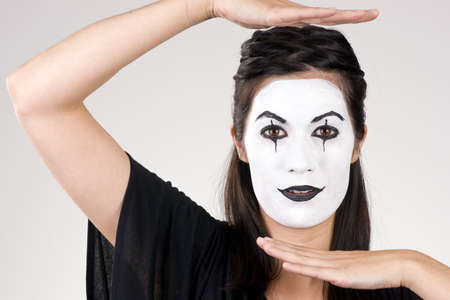 Woman made up in white face frames her features with her hands photo