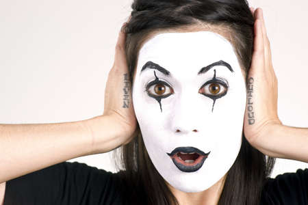 Woman made up in white face frames her features with her hands