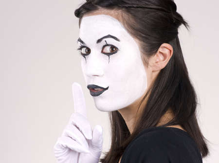 Woman made up in white face frames mouth with index finger
