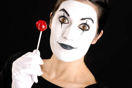 Woman made up in white face holds red sweet lollipop photo