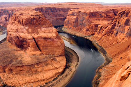 Boats carry travelers far below the ridge in the Colorado River photo