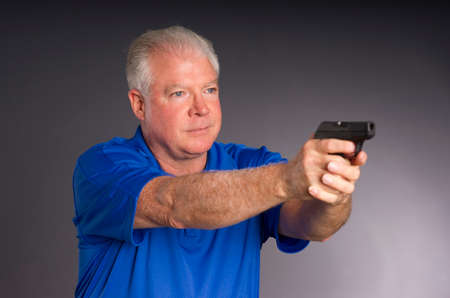 concealed: Man points small caliber semi automatic handgun to off camera right