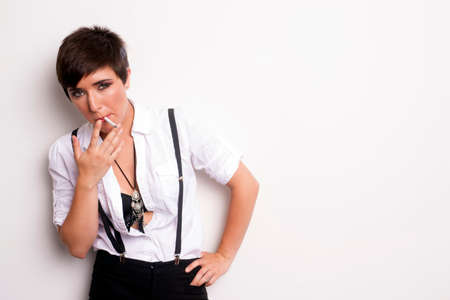 Woman with a look of Androgyny smokes a cigarette photo