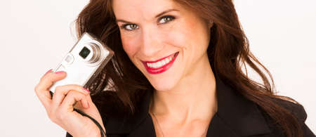 A woman holds camera off to the side smiling at viewer Stock Photo - 22763619