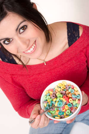 Female sits cross legged eating cereal in milk photo