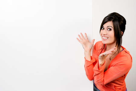 Very excited woman stands next to blank white space photo