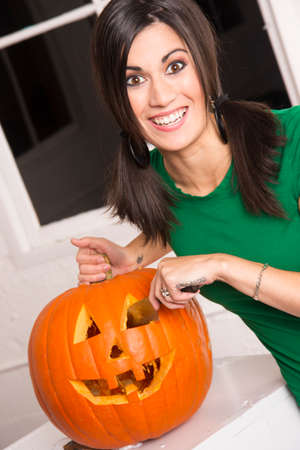 Excited woman prepares Halloween Pumkin carving it with a knife photo