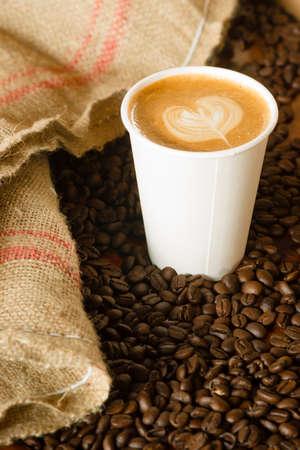 caf� � emporter: Tasse de caf� sur le comptoir avec des haricots r�tis