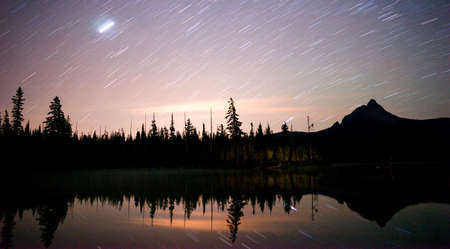 stargazing: A long exposure over water of the night sky in the mountains