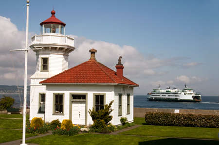 A ferry leaves the dock behind a coastal nautical beacon on puget sound Reklamní fotografie