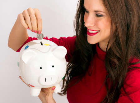 Woman in red placing a coin in a Piggy Bank