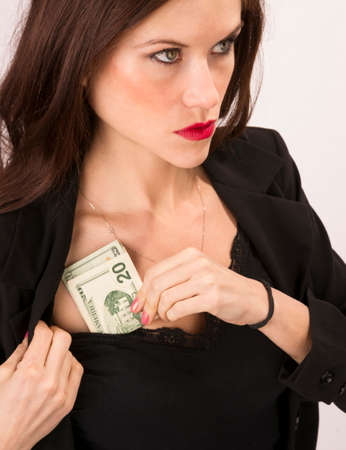 A good looking brunette woman stuffs money into her shirt Stock Photo - 23184442