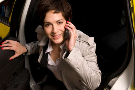 gets: A woman smiling as she gets out of taxi cab simultaniously talking on cell phone Stock Photo