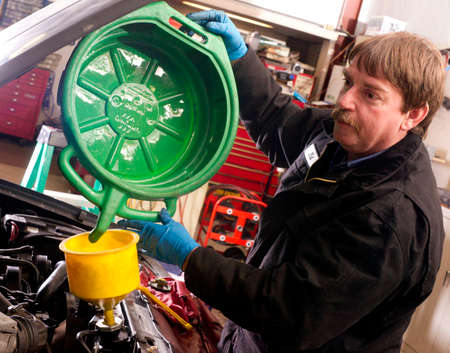 refills: Ed refills radiator with coolant after servicing it Stock Photo
