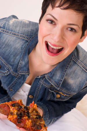 A very excited female enjoys a supreme meat crispy pizza photo