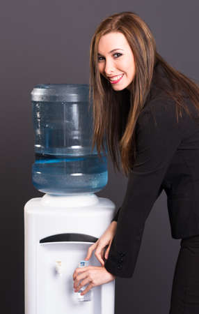 rehydration: Young adult female at water cooler in workplace