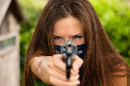 Seriuos looking woman in face mask points gun at you Stock Photo