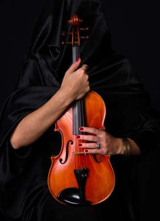 treasured: Woman draped in black holds her treasured violin musical instrument