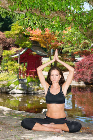 Slender woman smiles while practicing Yoga outdoors in the park