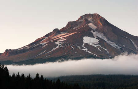 mount hood: An almost square piece of snow sits on the side of Mount Hood man made for people to ski on