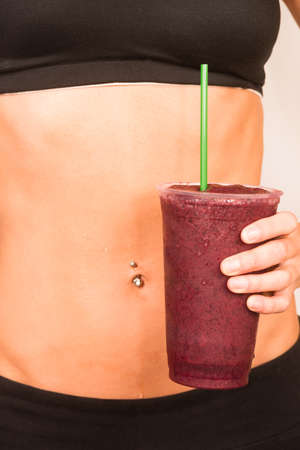 Woman holds a Berry Fruit Smoothie Waist Level Showing Healthy Slender Body photo