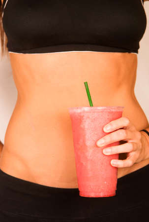 Woman holds Green Fruit Smoothie Waist Level Showing Healthy Slender Body photo