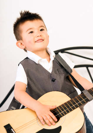 a guitarist boy playing guitar: This boy might want to be a musician when he grows up