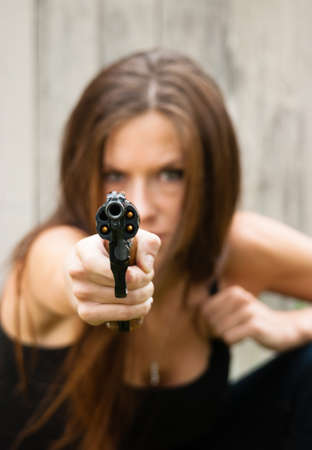 Woman crouches and prepares to fire second shot at assailant  Stock Photo