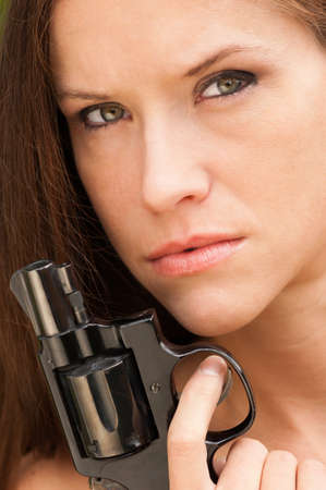 Woman holds revolver up to her face during a range session photo