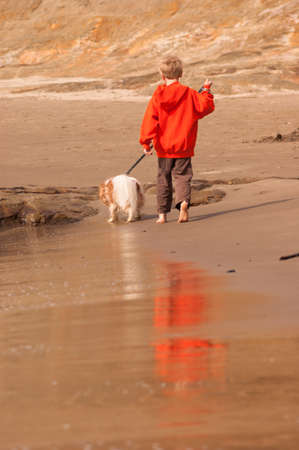 Beautiful beach scene young boy walking his dog photo