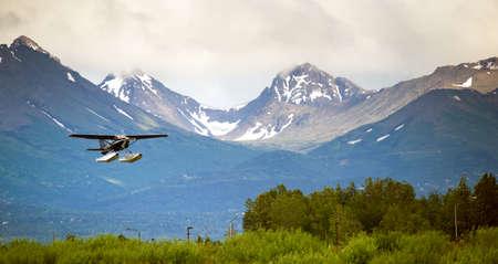 ブッシュの平面がバック グラウンドでチューガッチ山脈とアラスカの着陸を実行します。 写真素材