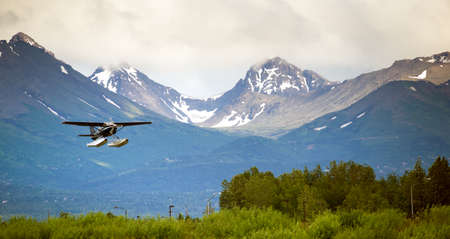 A bush plane performs landing in Alaska with Chugach Mountains in the Background
