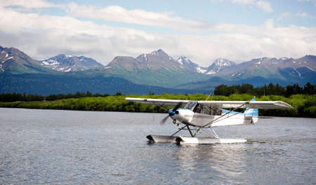 A bush plane performs taxi in in Alaska with Chugach Mountains in the Background Foto de archivo