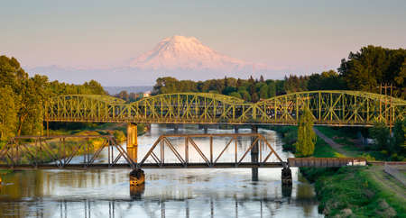 The Puyallup River meanders down from the glaciers on Mount Rainier under bridges through cities on it