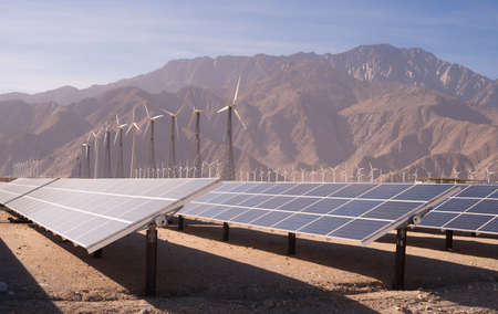 A large solar power farm with wind turbines in the background