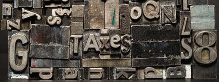 Old printing press typeset spells TAXES