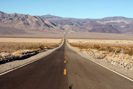 allowing: The road dips down allowing long visabilty in Death Valley Stock Photo
