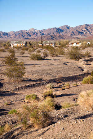 Dry ground and sage brush inhabit the foreground with abandoned buildings in the background photo