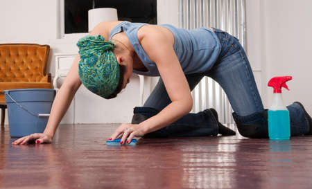A woman tries to finish cleaning the floor by hand Foto de archivo
