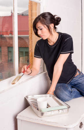 wife beater: Happy creative woman preparing to paint her window frames