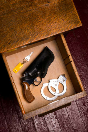 38 caliber: Dark Office and 38 Revolver in Desk Drawer with Handcuffs Stock Photo