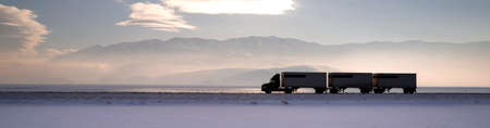 wasatch: Fresh snow covers the ground trucks pass late in the day on this lonely highway Stock Photo